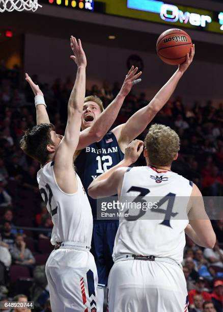 Eric Mika of the Brigham Young Cougars shoots against Dane Pineau and Jock Landale of the Saint Mary's Gaels during a semifinal game of the West...