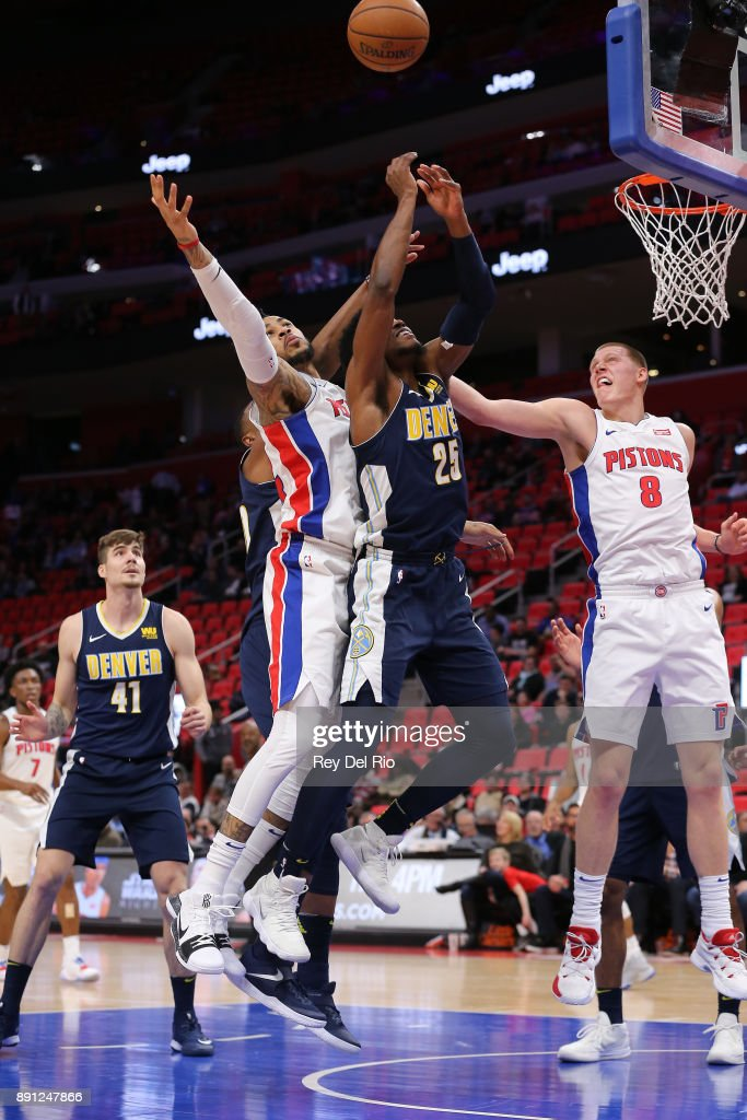 Eric Moreland #24 of the Detroit Pistons battles for a rebound against Malik Beasley #25 of the Denver Nuggets at Little Caesars Arena on December 12, 2017 in Detroit, Michigan.