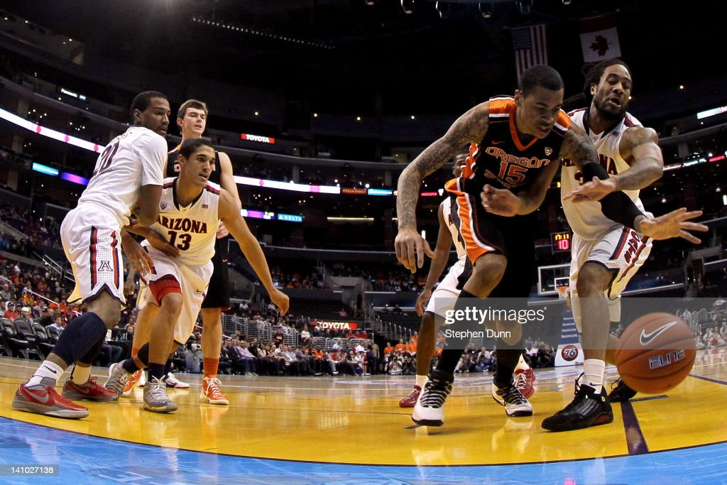 Eric Moreland #15 of the Oregon State Beavers attempts to save the ball alongside Jesse Perry #33 of the Arizona Wildcats in the first half in the semifinals of the 2012 Pacific Life Pac-12 men's basketball tournament at Staples Center on March 9, 2012 in Los Angeles, California.