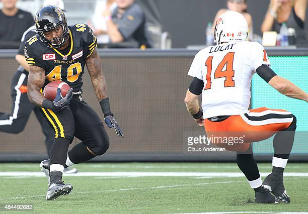 Eric Norwood of the Hamilton TigerCats gets set to step around quarterback Trvais Lulay of the BC Lions for a touchdown during a CFL football game at...