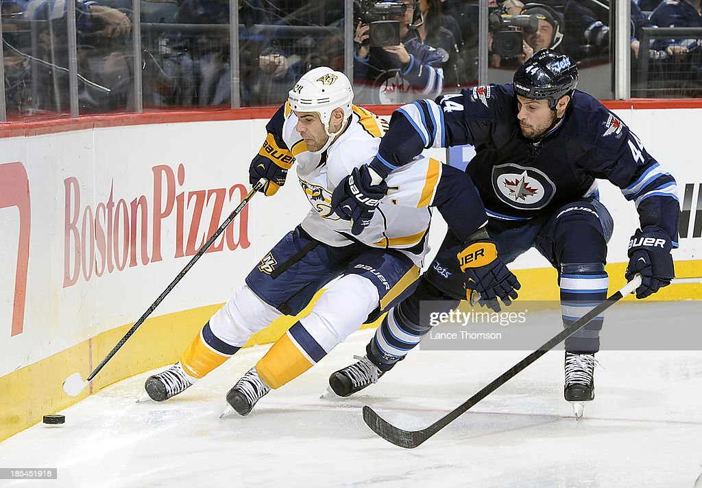 <a gi-track='captionPersonalityLinkClicked' href=/galleries/search?phrase=Eric+Nystrom&family=editorial&specificpeople=2209813 ng-click='$event.stopPropagation()'>Eric Nystrom</a> #24 of the Nashville Predators plays the puck away from defenseman <a gi-track='captionPersonalityLinkClicked' href=/galleries/search?phrase=Zach+Bogosian&family=editorial&specificpeople=4195061 ng-click='$event.stopPropagation()'>Zach Bogosian</a> #44 of the Winnipeg Jets during third period action at the MTS Centre on October 20, 2013 in Winnipeg, Manitoba, Canada.