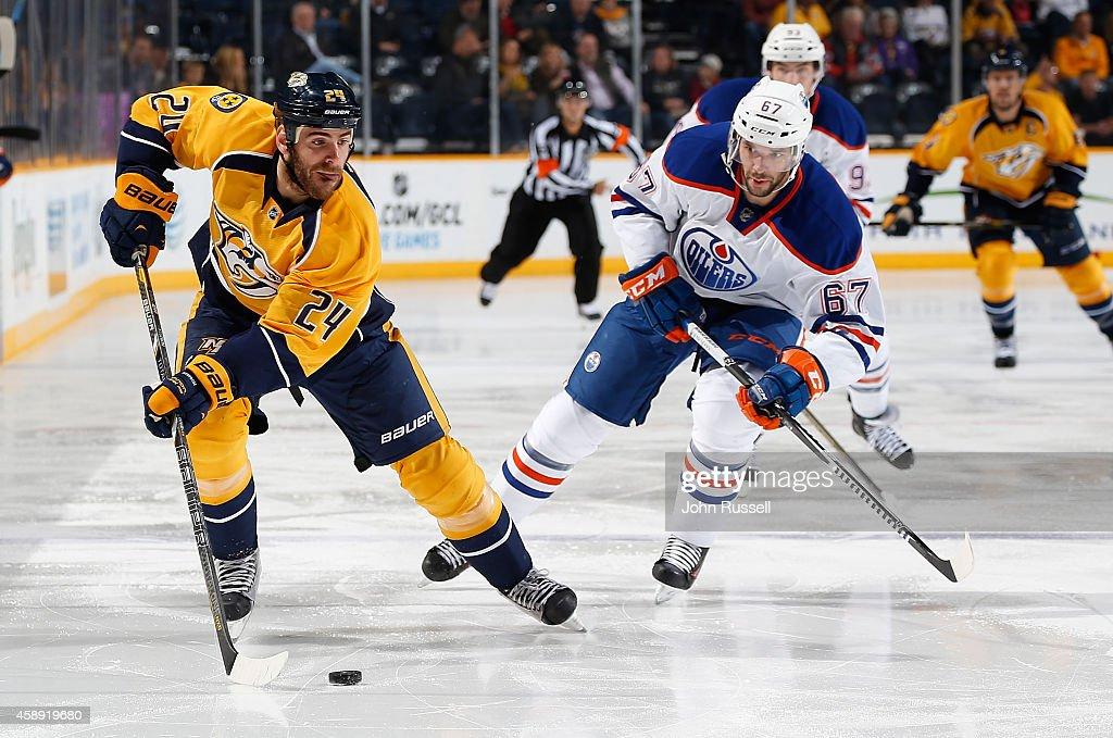 Eric Nystrom of the Nashville Predators skates against Benoit Pouliot of the Edmonton Oilers at Bridgestone Arena on November 11 2014 in Nashville...