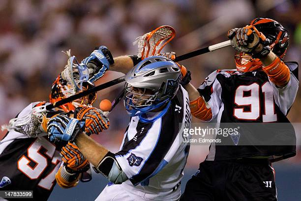 Eric O'Brien of the Ohio Machine has the ball knocked away by Peet Poillon and Dillon Roy of the Denver Outlaws during the fourth quarter at Sports...