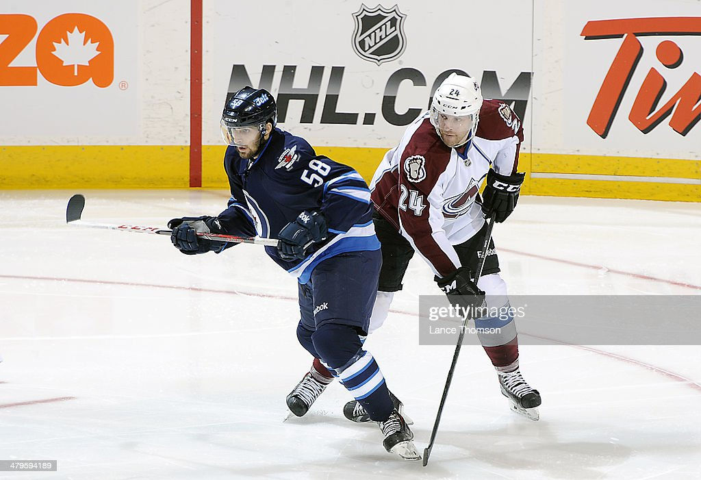 Eric O'Dell #58 of the Winnipeg Jets and Marc-Andre Cliche #24 of the Colorado Avalanche keep an eye on the play during second-period action at the MTS Centre on March 19, 2014 in Winnipeg, Manitoba, Canada.