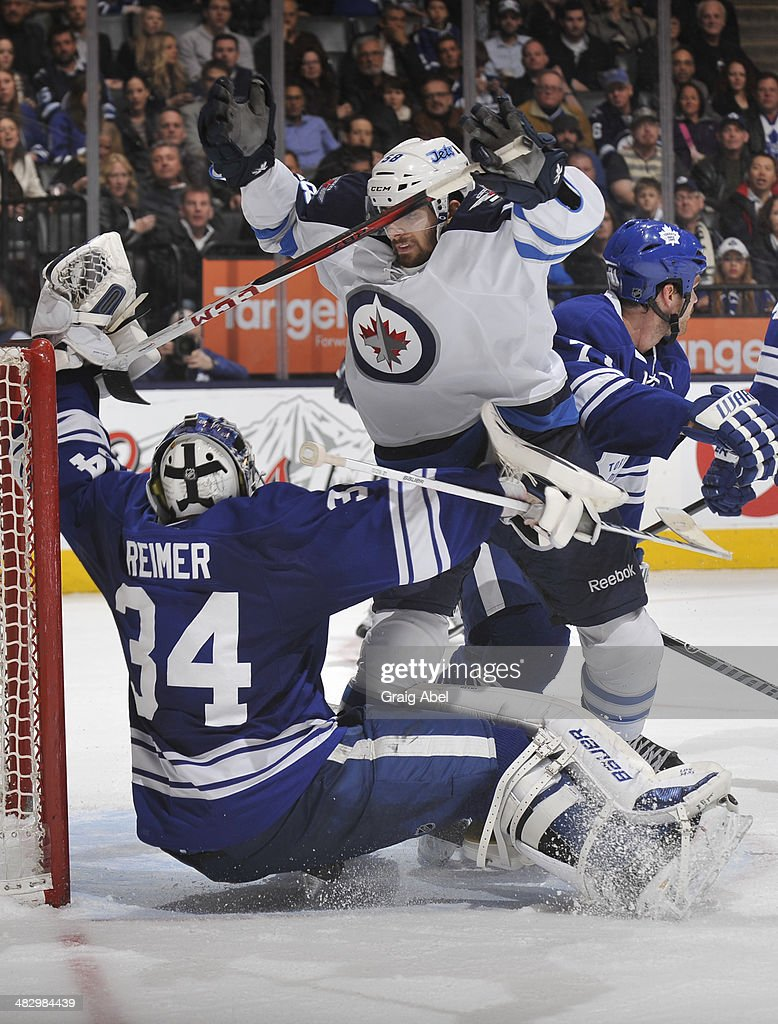 Eric O'Dell #58 of the Winnipeg Jets collides with James Reimer #34 of the Toronto Maple Leafs during NHL game action April 5, 2014 at the Air Canada Centre in Toronto, Ontario, Canada.