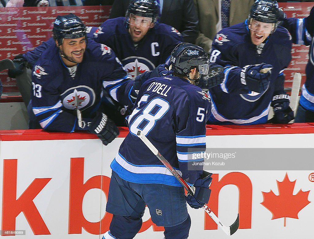 Eric O'Dell #58 of the Winnipeg Jets is congratulated by teammates <a gi-track='captionPersonalityLinkClicked' href=/galleries/search?phrase=Dustin+Byfuglien&family=editorial&specificpeople=672505 ng-click='$event.stopPropagation()'>Dustin Byfuglien</a> #33, <a gi-track='captionPersonalityLinkClicked' href=/galleries/search?phrase=Andrew+Ladd&family=editorial&specificpeople=228452 ng-click='$event.stopPropagation()'>Andrew Ladd</a> #16 and <a gi-track='captionPersonalityLinkClicked' href=/galleries/search?phrase=Bryan+Little&family=editorial&specificpeople=540533 ng-click='$event.stopPropagation()'>Bryan Little</a> #18 at the bench after scoring his first NHL goal against the Columbus Blue Jackets at the MTS Centre on January 11, 2014 in Winnipeg, Manitoba, Canada.