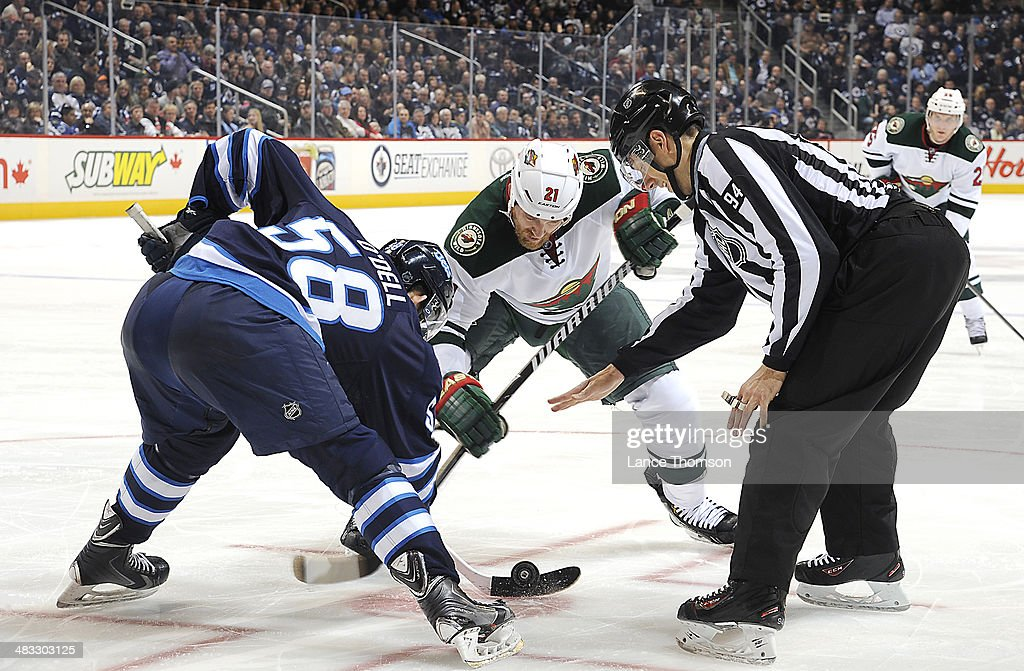 Eric O'Dell #58 of the Winnipeg Jets wins a third period face-off against <a gi-track='captionPersonalityLinkClicked' href=/galleries/search?phrase=Kyle+Brodziak&family=editorial&specificpeople=2165412 ng-click='$event.stopPropagation()'>Kyle Brodziak</a> #21 of the Minnesota Wild at the MTS Centre on April 7, 2014 in Winnipeg, Manitoba, Canada.