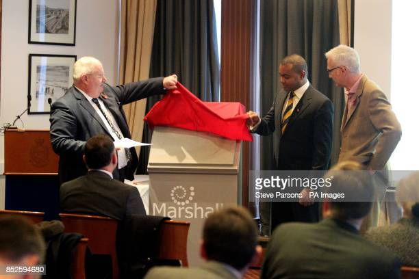 Eric Pickles Johnson Beharry with winner Charlie MacKeith unveil a paving stone at the Army and Navy Club in Central London which will commemorate...