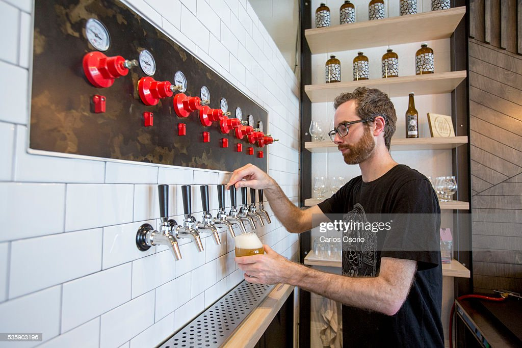 TORONTO, ON - MAY Eric pours a glass of beer. Callum Hay and Eric Portelance (glasses) are the co-founders of Halo Brewery in Toronto. May 30, 2016. For story on how craft breweries are banding together to survive, sharing ingredients and passing around knowledge