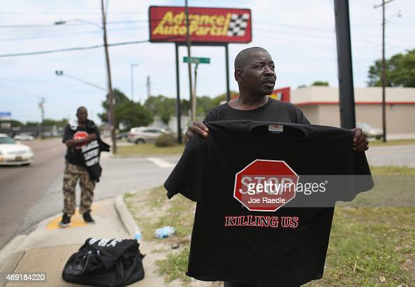 Eric Quattlebaum sells a shirt reading 'Stop Killing Us' near the spot where Walter Scott was killed on April 4th by a North Charleston police...