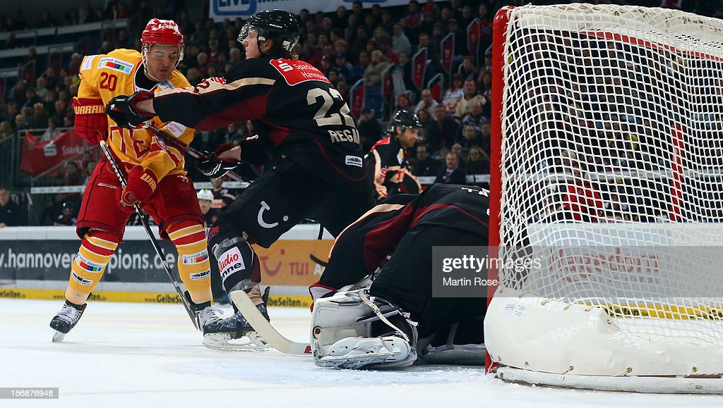 Eric Regan (C) of Hannover and battles for position with Manuel Strobel (L) of Duesseldorf in front of the net during the DEL match between Hannover Scorpions and Duesseldorfer EG at TUI Arena on November 23, 2012 in Hanover, Germany.