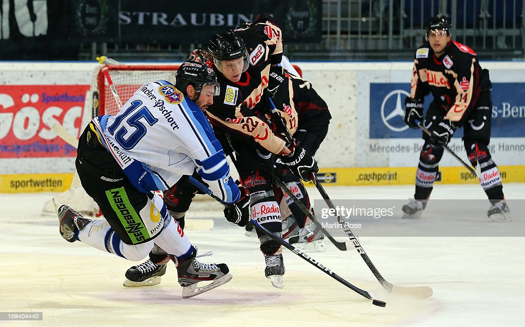 Eric Regan (R) of Hannover and Grant Lewis (L) of Straubing battle for the puck during the DEL match between Hannover Scorpions and Straubing Tigers at TUI Arena on January 13, 2013 in Hanover, Germany.
