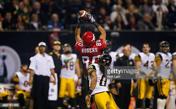 Eric Rogers of the Calgary Stampeders makes a catch while being defended against by Rico Murray of the Hamilton TigerCats during the first half of...
