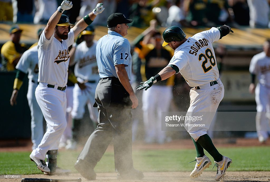 Eric Sogard #28 and Derek Norris #36 of the Oakland Athletics celebrates after Sogard scored the winning run on a throwing error from Manny Machado #13 of the Baltimore Orioles in the 10th inning at O.co Coliseum on April 28, 2013 in Oakland, California. The Athletics won the game 9-8.