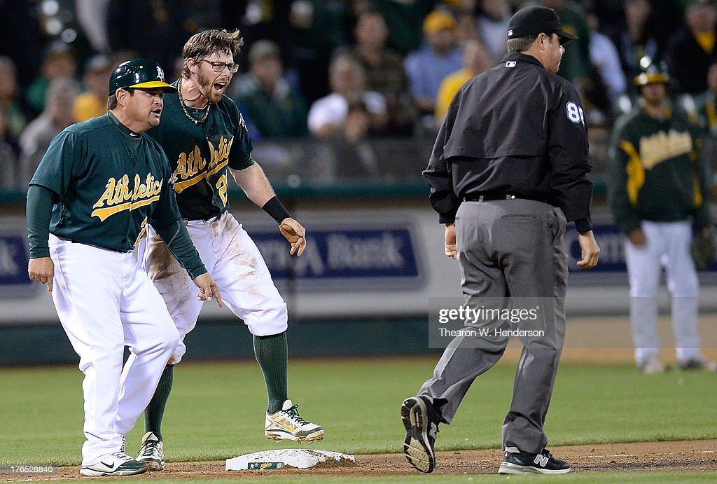 Eric Sogard #28 and third base coach Mike Gallego #2 reacts towards umpire Doug Eddings #88 after Sogard was called out at third base during the eighth inning against the Houston Astros at O.co Coliseum on August 14, 2013 in Oakland, California. Sogard tagged up and attempted to go to third from second on a fly ball to centerfield.