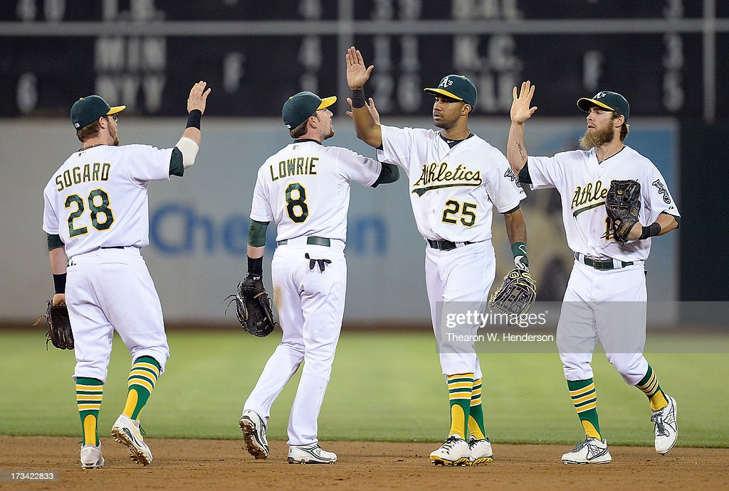 Eric Sogard #28, Jed Lowrie #8, Chris Young #25 and Josh Reddick #16 of the Oakland Athletics celebrate defeating the Boston Red Sox 3-0 at O.co Coliseum on July 13, 2013 in Oakland, California.