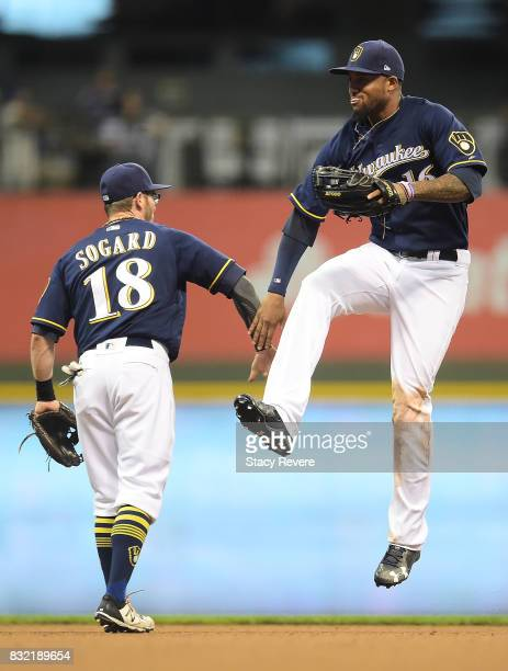 Eric Sogard of the Milwaukee Brewers and Domingo Santana celebrate a victory over the Pittsburgh Pirates at Miller Park on August 15 2017 in...