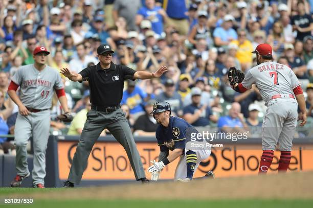 Eric Sogard of the Milwaukee Brewers beats a tag at third base by Eugenio Suarez of the Cincinnati Reds during the fourth inning against the...