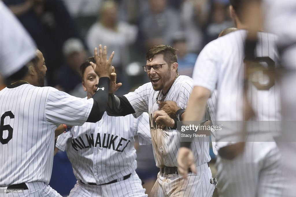 Eric Sogard #18 of the Milwaukee Brewers celebrtes with teammates after scoring on a wild pitch to win the game in the 10th inning against the Cincinnati Reds at Miller Park on August 12, 2017 in Milwaukee, Wisconsin.