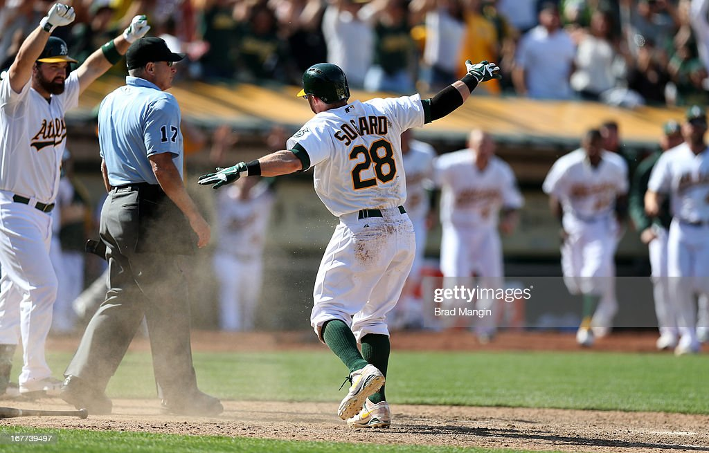 Eric Sogard #28 of the Oakland Athletics calls himself safe after sliding home safely with the winning run in the bottom of the 10th inning during the game against the Baltimore Orioles on Sunday, April 28, 2013 at The O.co Coliseum in Oakland, California.