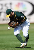 Eric Sogard of the Oakland Athletics commits an error bobbling this ball off the bat of Chase Utley of the Philadelphia Phillies in the top of the...