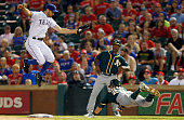 Eric Sogard of the Oakland Athletics dives into first base safe to beat the tag out by Adam Rosales of the Texas Rangers in the top of the fifth...