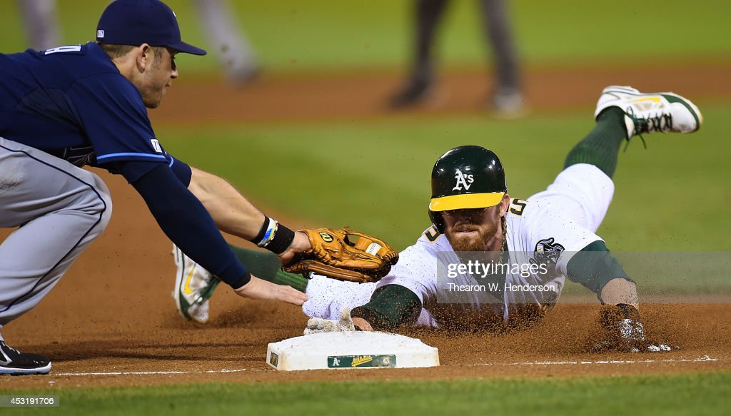 <a gi-track='captionPersonalityLinkClicked' href=/galleries/search?phrase=Eric+Sogard&family=editorial&specificpeople=6796459 ng-click='$event.stopPropagation()'>Eric Sogard</a> #28 of the Oakland Athletics dives into third base safe, beating the tag of <a gi-track='captionPersonalityLinkClicked' href=/galleries/search?phrase=Evan+Longoria&family=editorial&specificpeople=2349329 ng-click='$event.stopPropagation()'>Evan Longoria</a> #3 of the Tampa Bay Rays in the bottom of the fourth inning at O.co Coliseum on August 4, 2014 in Oakland, California. Sogard tagged up at second base on a fly ball to right field.