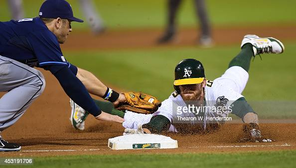 Eric Sogard of the Oakland Athletics dives into third base safe beating the tag of Evan Longoria of the Tampa Bay Rays in the bottom of the fourth...