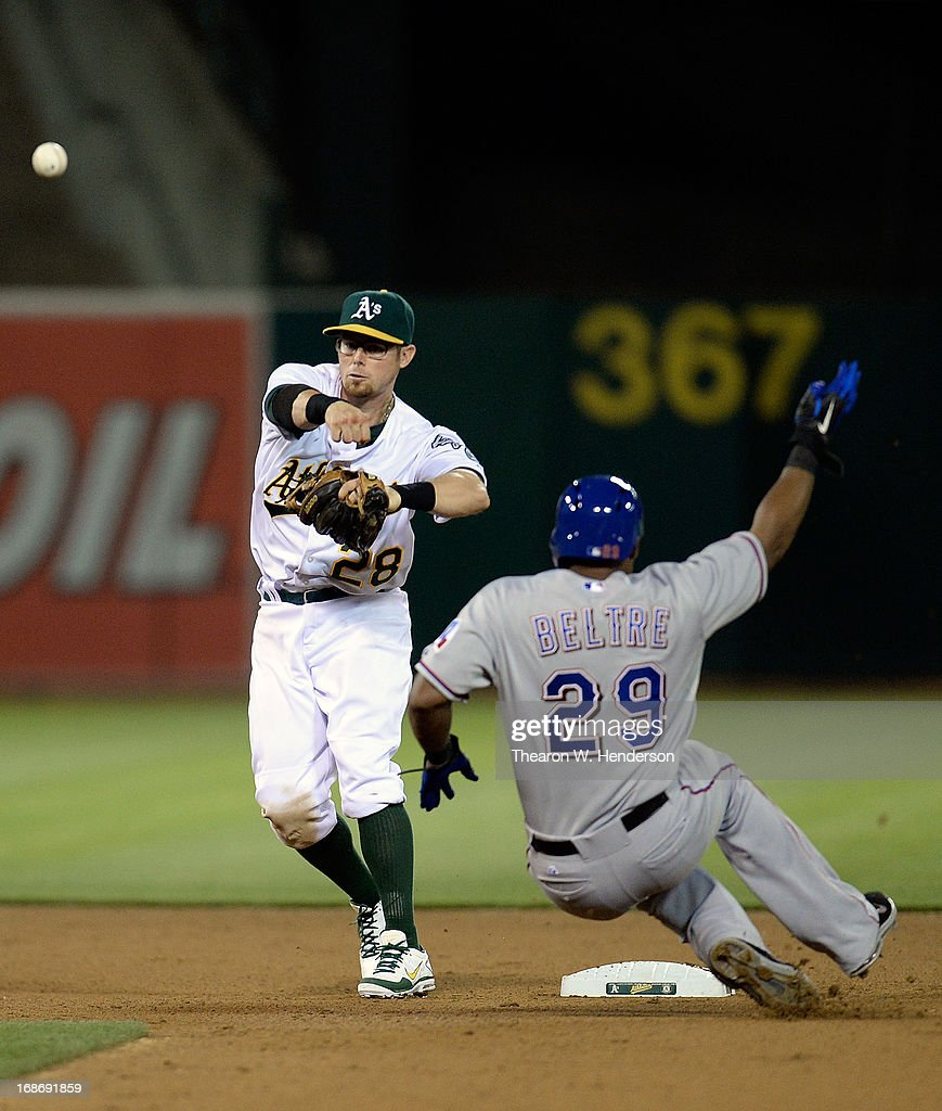 <a gi-track='captionPersonalityLinkClicked' href=/galleries/search?phrase=Eric+Sogard&family=editorial&specificpeople=6796459 ng-click='$event.stopPropagation()'>Eric Sogard</a> #28 of the Oakland Athletics gets his throw off to complete the double play, while avoiding the slide of <a gi-track='captionPersonalityLinkClicked' href=/galleries/search?phrase=Adrian+Beltre&family=editorial&specificpeople=202631 ng-click='$event.stopPropagation()'>Adrian Beltre</a> #29 of the Texas Rangers in the seventh inning at O.co Coliseum on May 13, 2013 in Oakland, California.