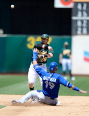 Eric Sogard of the Oakland Athletics gets his throw off to complete the doubleplay as Jose Bautista of the Toronto Blue Jays slides into second base...