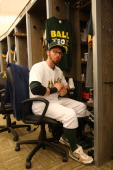 Eric Sogard of the Oakland Athletics gets ready in the clubhouse prior to the game against the St Louis Cardinals at Oco Coliseum on June 30 2013 in...