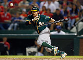 Eric Sogard of the Oakland Athletics hits a bunt against the Texas Rangers in the top of the fifth inning at Globe Life Park in Arlington on...