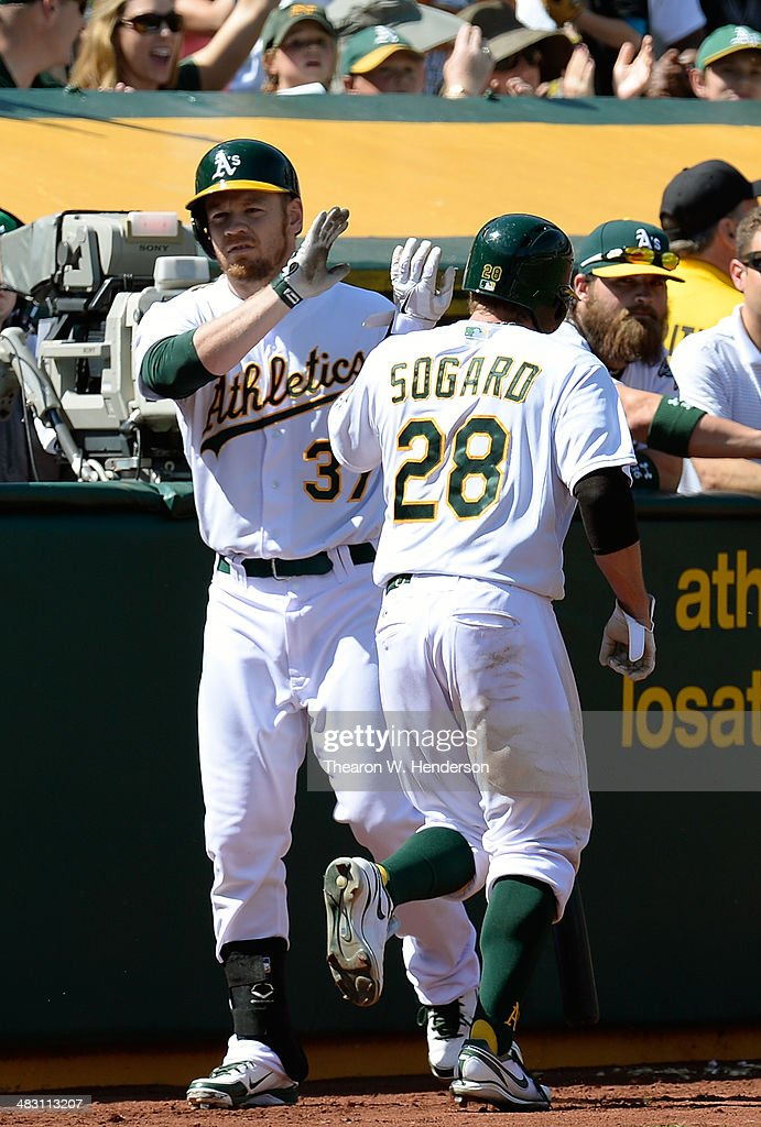 Eric Sogard #28 of the Oakland Athletics is congratulated by Brandon Moss #37 after Sogard scored against the Seattle Mariners in the bottom of the fifth inning at O.co Coliseum on April 6, 2014 in Oakland, California. Sogard scored on a Josh Donaldson RBI Single