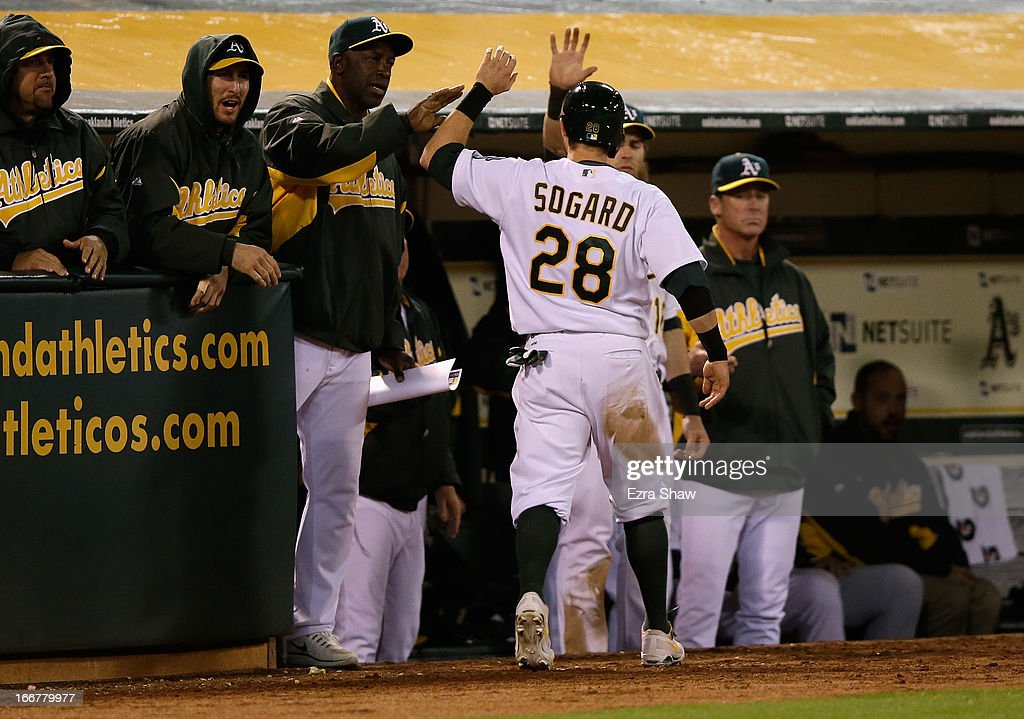 Eric Sogard #28 of the Oakland Athletics is congratulated by teammates after he scored on a triple by Coco Crisp #4 in the fifth inning of their game against the Houston Astros at O.co Coliseum on April 16, 2013 in Oakland, California.