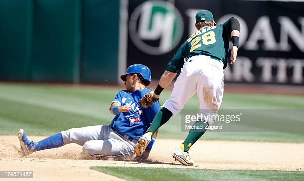Eric Sogard of the Oakland Athletics tags Maicer Izturis of the Toronto Blue Jays out at second during the game at Oco Coliseum on July 31 2013 in...