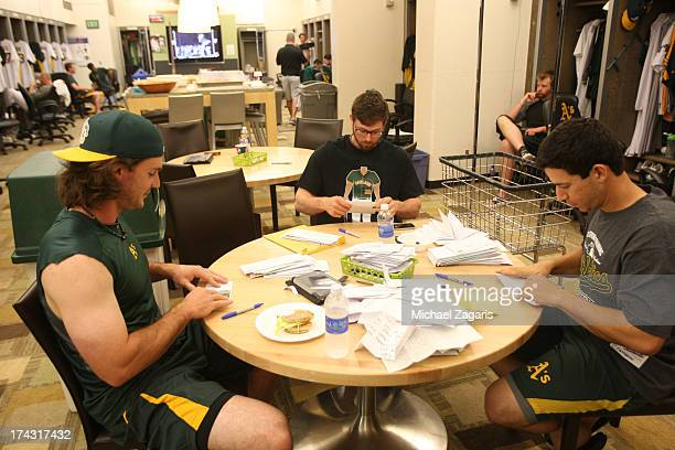 Eric Sogard Tommy Milone and John Jaso of the Oakland Athletics go through fan mail in the clubhouse prior to the game against the Boston Red Sox at...