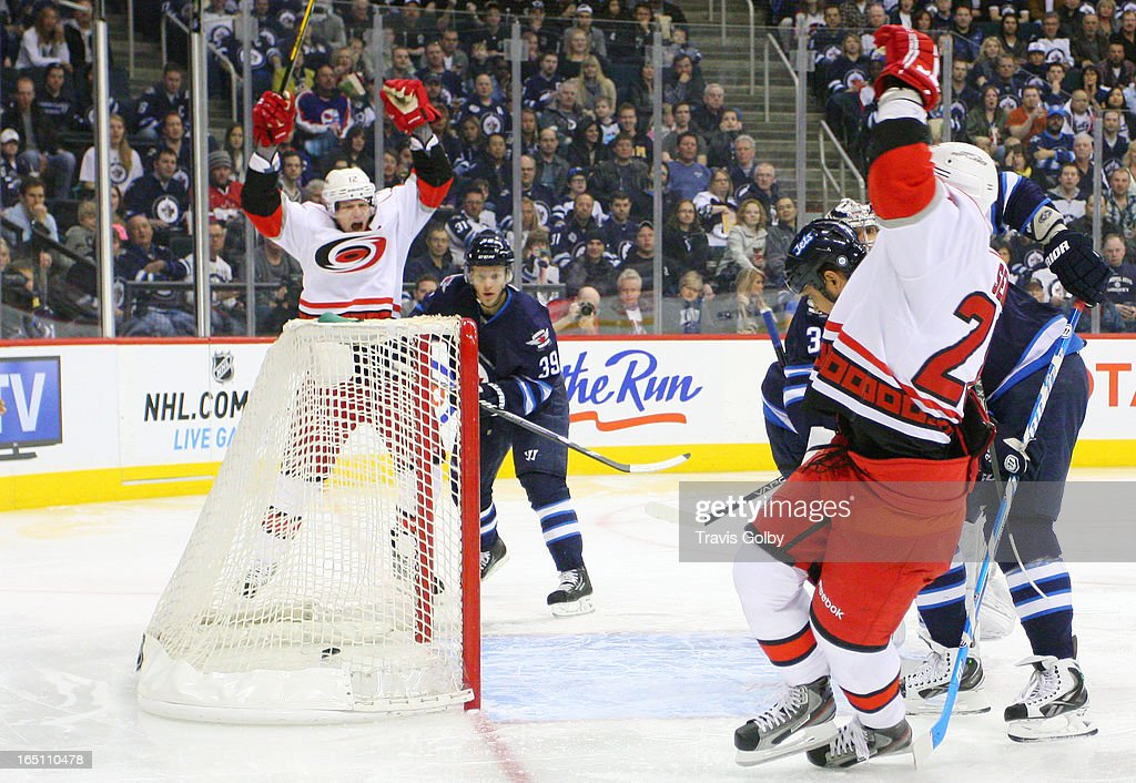 <a gi-track='captionPersonalityLinkClicked' href=/galleries/search?phrase=Eric+Staal&family=editorial&specificpeople=202199 ng-click='$event.stopPropagation()'>Eric Staal</a> #12 and <a gi-track='captionPersonalityLinkClicked' href=/galleries/search?phrase=Alexander+Semin&family=editorial&specificpeople=206654 ng-click='$event.stopPropagation()'>Alexander Semin</a> #28 of the Carolina Hurricanes throw their arms up in celebration after a scoring a first-period goal against the Winnipeg Jets at the MTS Centre on March 30, 2013 in Winnipeg, Manitoba, Canada.