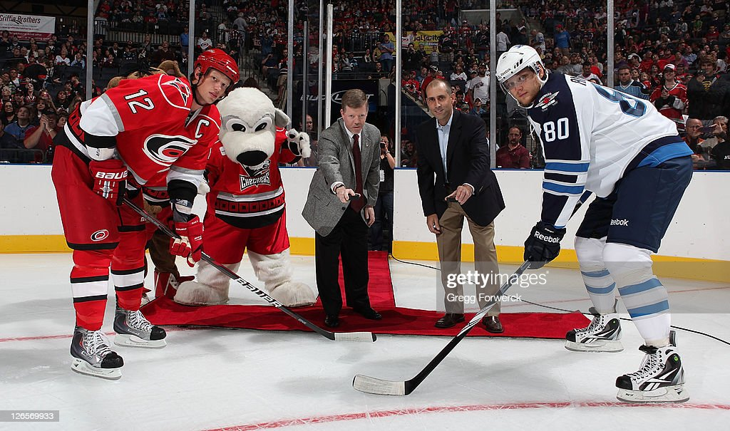 Eric Staal #12 of the Carolina Hurricanes and Nik Antropov #80 of the Winnipeg Jets meet for the ceremonial puck drop by Charlotte Checkers CEO Michael Kahn and John Marchiando Vice President of Marketing North America for Husqvarna during an NHL preseason game on September 25, 2011 at Time Warner Arena in Charlotte, North Carolina.