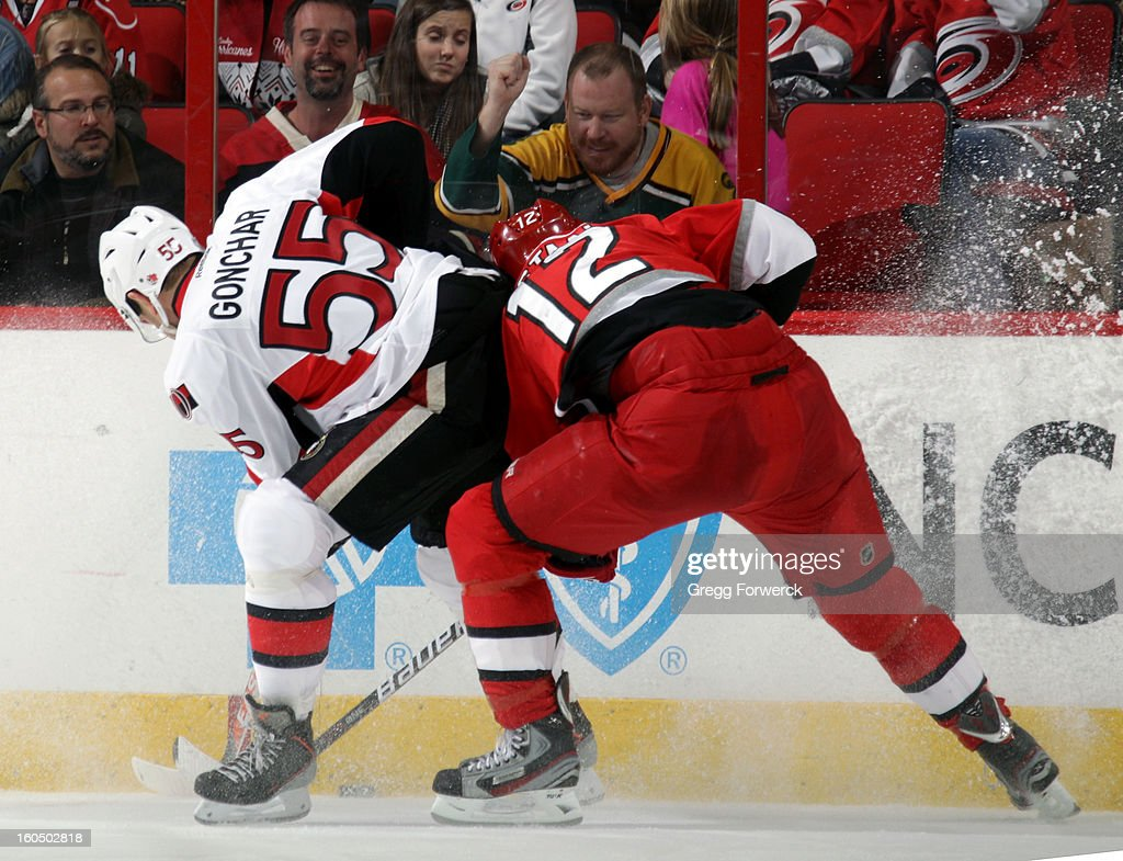 Eric Staal #12 of the Carolina Hurricanes and Sergei Gonchar #55 of the Ottawa Senators chase the puck into the boards during their NHL game at PNC Arena on February 1, 2013 in Raleigh, North Carolina.