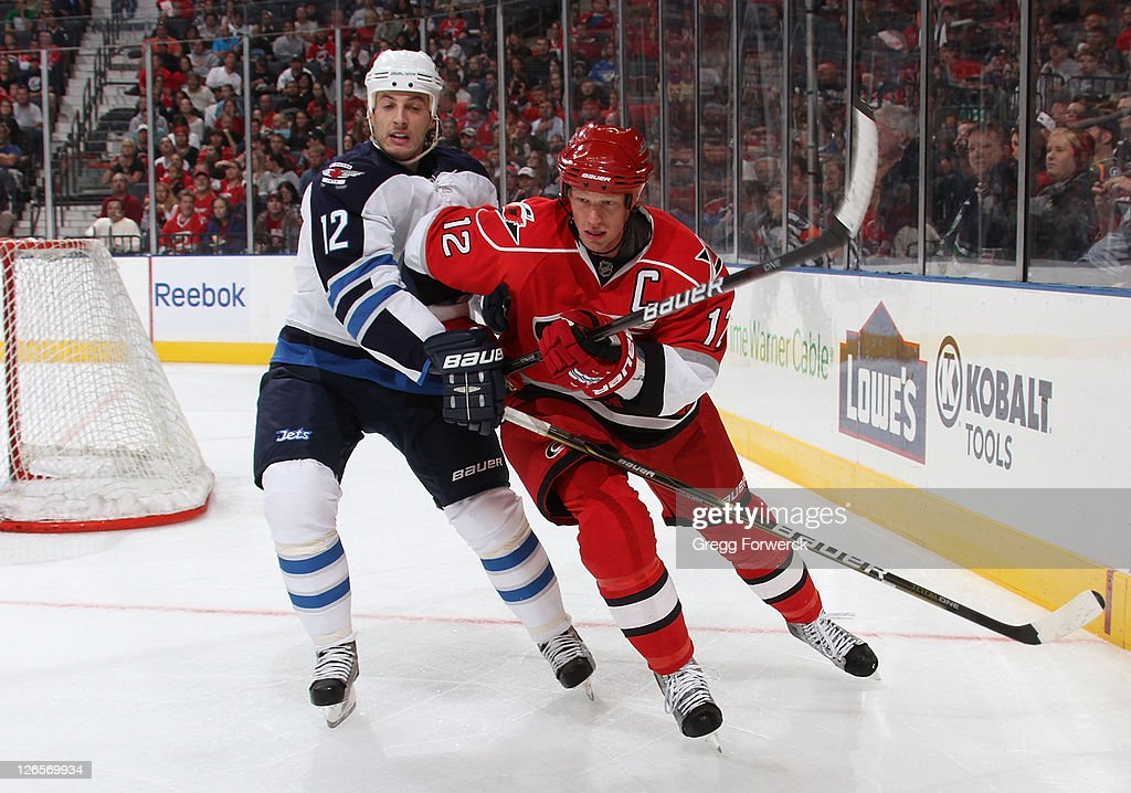 <a gi-track='captionPersonalityLinkClicked' href=/galleries/search?phrase=Eric+Staal&family=editorial&specificpeople=202199 ng-click='$event.stopPropagation()'>Eric Staal</a> #12 of the Carolina Hurricanes battles for position against Randy Jones #12 of the Winnipeg Jets during an NHL preseason game on September 25, 2011 at Time Warner Arena in Charlotte, North Carolina.