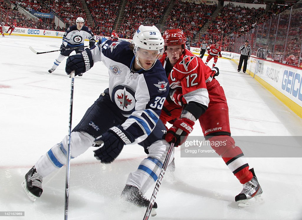 <a gi-track='captionPersonalityLinkClicked' href=/galleries/search?phrase=Eric+Staal&family=editorial&specificpeople=202199 ng-click='$event.stopPropagation()'>Eric Staal</a> #12 of the Carolina Hurricanes battles in the corner with <a gi-track='captionPersonalityLinkClicked' href=/galleries/search?phrase=Tobias+Enstrom&family=editorial&specificpeople=2538468 ng-click='$event.stopPropagation()'>Tobias Enstrom</a> #39 of the Winnipeg Jets during an NHL game on March 30, 2012 at PNC Arena in Raleigh, North Carolina.