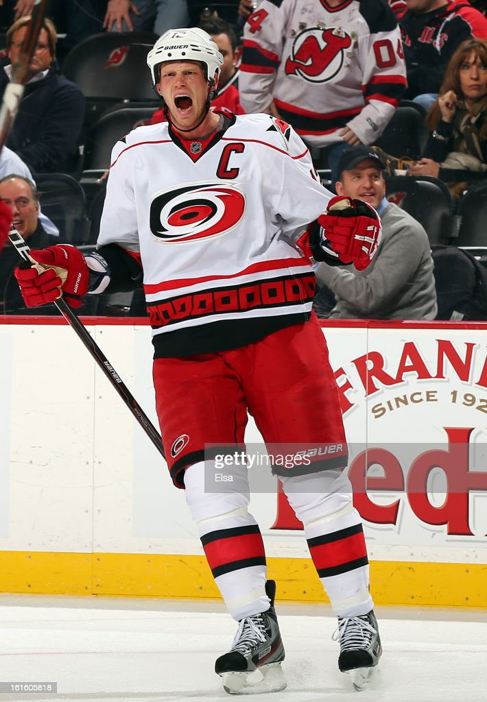 Eric Staal #12 of the Carolina Hurricanes celebrates the empty net goal by teammate Jiri Tlusty in the third period against the New Jersey Devils at the Prudential Center on February 12, 2013 in Newark, New Jersey.The Carolina Hurricanes defeated the New Jersey Devils 4-2.