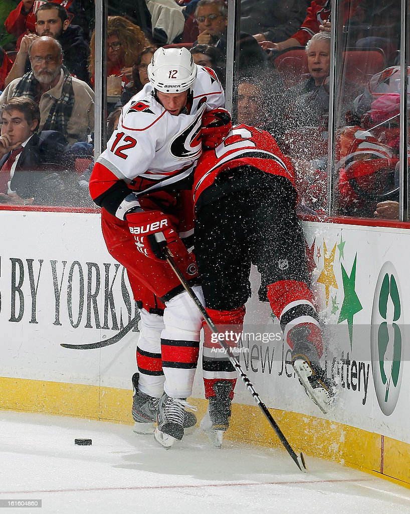 Eric Staal #12 of the Carolina Hurricanes checks Andy Greene #6 of the New Jersey Devils into the boards during the game at the Prudential Center on February 12, 2013 in Newark, New Jersey.