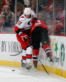 Eric Staal of the Carolina Hurricanes checks Andy Greene of the New Jersey Devils into the boards during the game at the Prudential Center on...