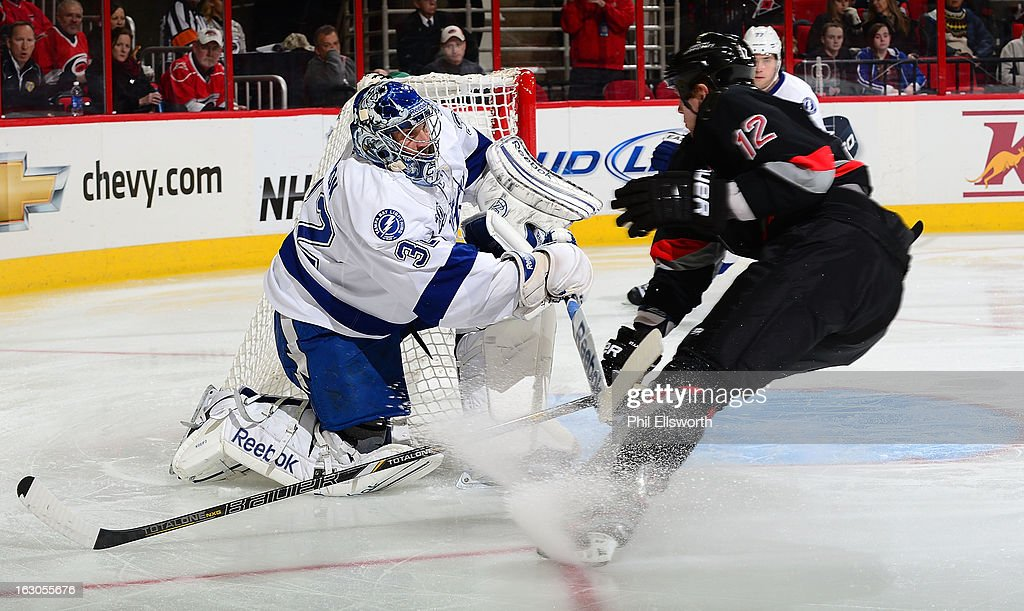 <a gi-track='captionPersonalityLinkClicked' href=/galleries/search?phrase=Eric+Staal&family=editorial&specificpeople=202199 ng-click='$event.stopPropagation()'>Eric Staal</a> #12 of the Carolina Hurricanes clashes with <a gi-track='captionPersonalityLinkClicked' href=/galleries/search?phrase=Mathieu+Garon&family=editorial&specificpeople=206119 ng-click='$event.stopPropagation()'>Mathieu Garon</a> #32 of the Tampa Bay Lightning during an NHL game on February 23, 2013 at PNC Arena in Raleigh, North Carolina.