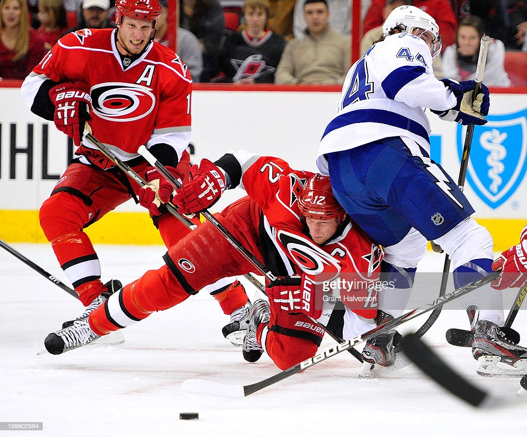 <a gi-track='captionPersonalityLinkClicked' href=/galleries/search?phrase=Eric+Staal&family=editorial&specificpeople=202199 ng-click='$event.stopPropagation()'>Eric Staal</a> #13 of the Carolina Hurricanes collides with Nate Thompson #44 of the Tampa Bay Lightning during play at PNC Arena on January 22, 2013 in Raleigh, North Carolina.