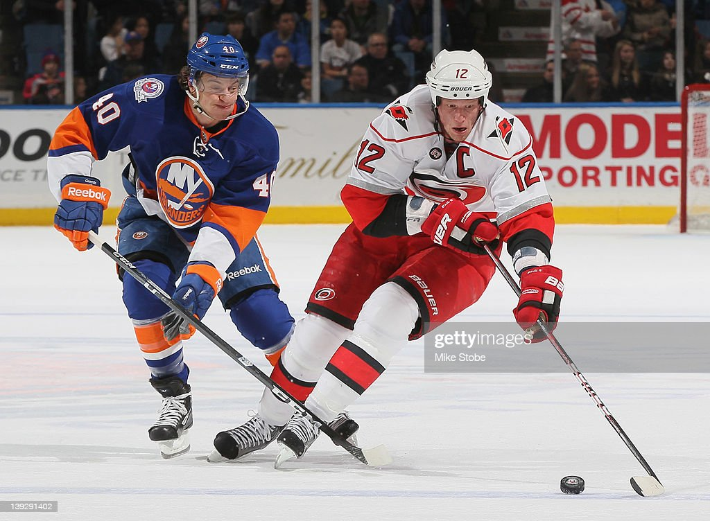 <a gi-track='captionPersonalityLinkClicked' href=/galleries/search?phrase=Eric+Staal&family=editorial&specificpeople=202199 ng-click='$event.stopPropagation()'>Eric Staal</a> #12 of the Carolina Hurricanes controls the puck in front of <a gi-track='captionPersonalityLinkClicked' href=/galleries/search?phrase=Michael+Grabner&family=editorial&specificpeople=537955 ng-click='$event.stopPropagation()'>Michael Grabner</a> #40 of the New York Islanders at Nassau Veterans Memorial Coliseum on February 18, 2012 in Uniondale, New York. The Islanders defeated the Hurricanes 4-3.