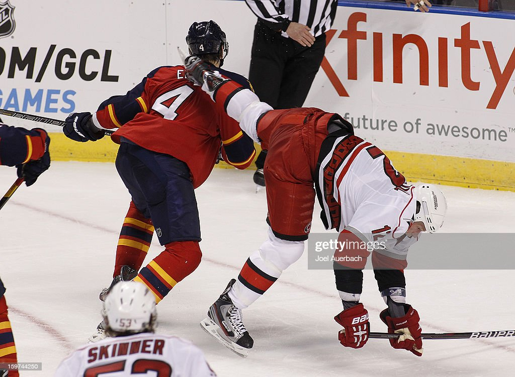 Eric Staal #12 of the Carolina Hurricanes falls over Keaton Ellerby #4 of the Florida Panthers during the seasons opener at the BB&T Center on January 19, 2013 in Sunrise, Florida. The Panthers defeated the Hurricanes 5-1.