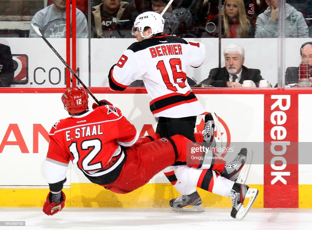 <a gi-track='captionPersonalityLinkClicked' href=/galleries/search?phrase=Eric+Staal&family=editorial&specificpeople=202199 ng-click='$event.stopPropagation()'>Eric Staal</a> #12 of the Carolina Hurricanes falls to the ice after becoming tangled with <a gi-track='captionPersonalityLinkClicked' href=/galleries/search?phrase=Steve+Bernier&family=editorial&specificpeople=557040 ng-click='$event.stopPropagation()'>Steve Bernier</a> #18 of the New Jersey Devils during their NHL game at PNC Arena on March 21, 2013 in Raleigh, North Carolina.