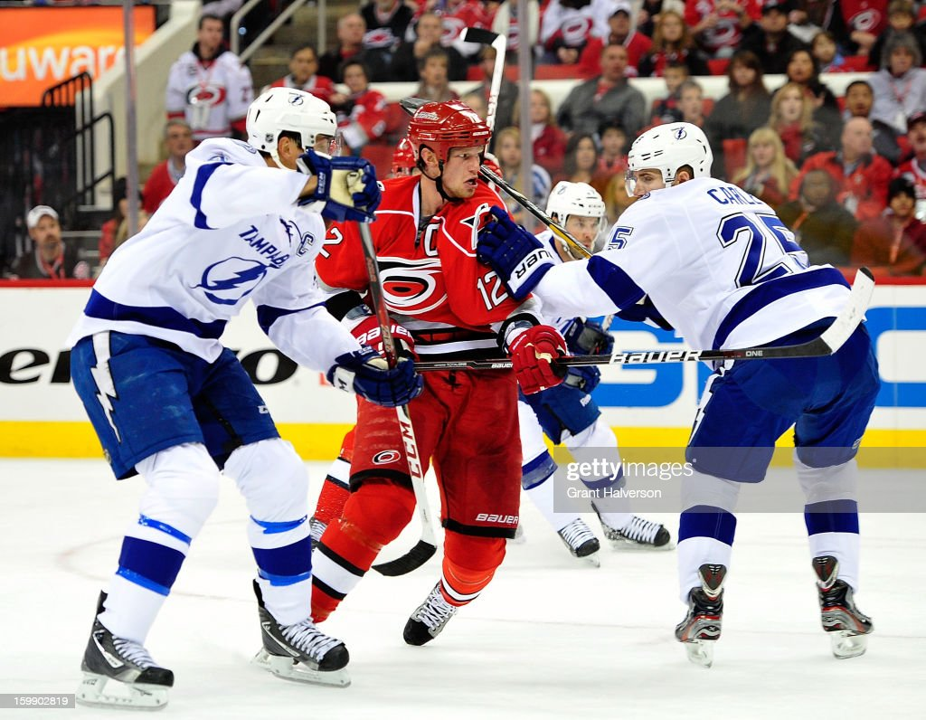 Eric Staal #12 of the Carolina Hurricanes fights through the Tampa Bay Lightning defense during play at PNC Arena on January 22, 2013 in Raleigh, North Carolina.
